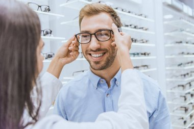 Partial view of female optometrist putting on eyeglasses on smiling man in optics stock vector