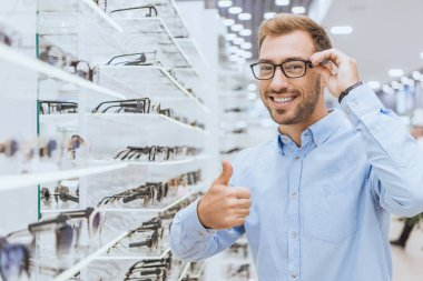 happy young man choosing eyeglasses and doing thumb up gesture in optica
