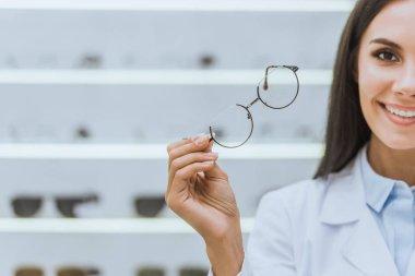 Attractive smiling optometrist holding eyesight in optica stock vector