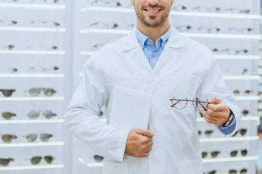 cropped view of optometrist in white coat holding eyeglasses and digital tablet in optica