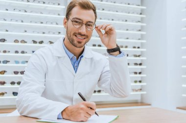 professional doctor in white coat writing diagnosis in optica