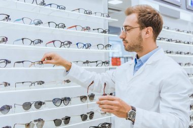 Professional oculist taking eyeglasses from shelves in ophthalmic shop stock vector