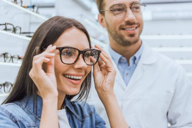 portrait of smiling woman choosing eyeglasses while male optometrist standing near in optics
