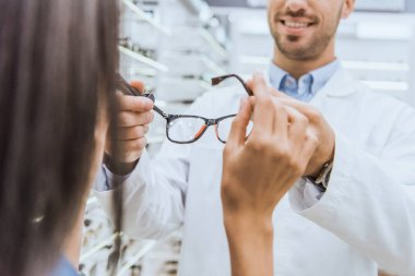 partial view of male oculist giving eyeglasses to woman in ophthalmic shop