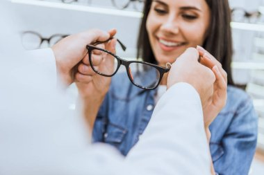 cropped image of male oculist giving eyeglasses to woman in optics