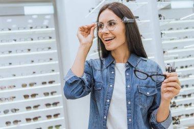 Smiling attractive woman choosing eyeglasses in optics stock vector