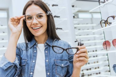 portrait of attractive happy woman choosing eyeglasses and looking at camera in ophthalmic shop
