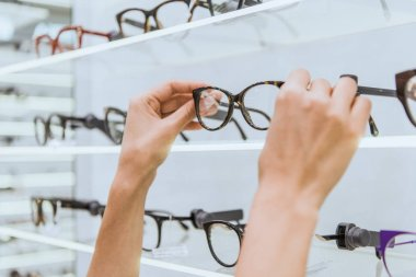 partial view of optician taking glasses from shelf in ophthalmic shop