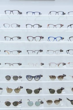 shelves with stylish glasses and trendy sunglasses in ophthalmic shop