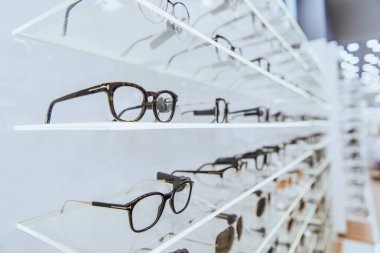 selective focus of white shelves with stylish glasses in ophthalmology