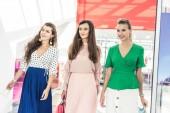 Fényképek mosolygó fiatal nők gazdaság papír táskák, és nézett shopping mall