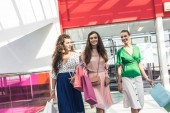 mosolygó fiatal Szépasszony papírzacskó beszél, és a gyaloglás a shopping mall