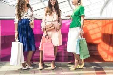 cropped shot of smiling stylish girls holding paper bags and standing together in shopping mall