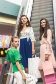 Fotografie krásné usměvavé mladé ženy s papírové tašky stojící na eskalátoru v nákupní centrum
