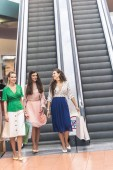 smiling stylish young women holding paper bags and walking near escalator in shopping mall