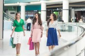 Fotografie beautiful smiling young women holding shopping bags and walking together in mall