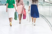 back view of stylish girls in skirts and high heeled shoes holding paper bags and walking in shopping mall