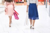 Fotografie cropped shot of stylish girls holding paper bags and walking in shopping mall