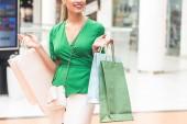 Fotografia ritagliata colpo di elegante giovane donna felice che tiene i sacchetti di carta nel centro commerciale