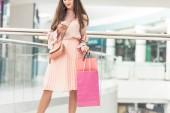 Oříznout záběr stylová holka drží nákupní tašky a pomocí smartphone v obchoďáku