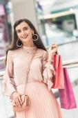 Fotografie krásná usměvavá mladá žena držící papírové tašky v nákupní centrum