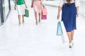 cropped shot of stylish young women in skirts and high heeled shoes walking with shopping bags in mall
