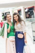 Fotografie beautiful stylish young women holding shopping bags and smiling at camera in mall
