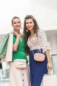Fotografie krásné stylové dívky drží nákupní tašky a usmívá se na kameru v obchoďáku