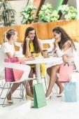 Fényképek szép mosolygó fiatal nő iszik kávé papírpohár, és beszél ülve, bevásárlóközpont, kávézó