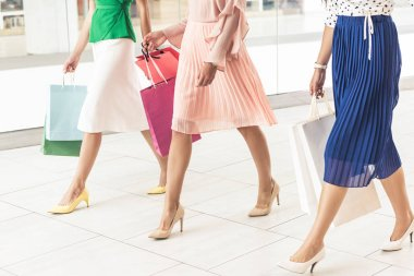 low section of stylish girls in high heeled shoes walking with paper bags in shopping mall