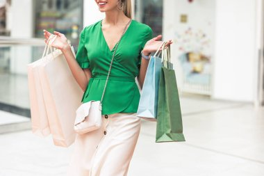 cropped shot of smiling young woman holding paper bags and walking in shopping mall