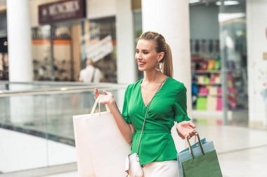 beautiful smiling blonde girl holding paper bags and looking away in shopping mall