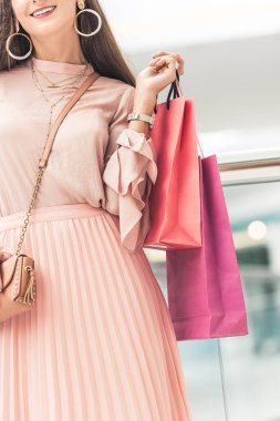 cropped shot of stylish smiling girl holding paper bags in shopping mall