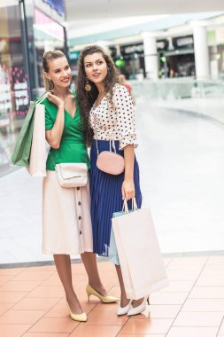 beautiful smiling girls holding paper bags and looking away while standing together in shopping mall