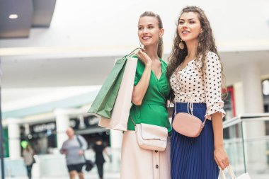 beautiful smiling girls holding paper bags and looking away in shopping mall