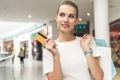krásná usměvavá mladá žena držící papírové tašky a kreditní karty v nákupní centrum