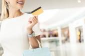 Fotografie Oříznout záběr usměvavé mladé ženy držící kreditní kartu v nákupní centrum