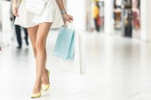 Fotografie low section of stylish girl holding paper bags and walking in shopping mall