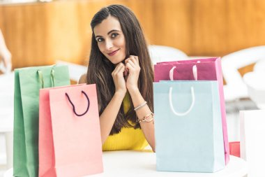 beautiful young woman sitting at table with shopping bags and smiling at camera