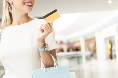cropped shot of smiling young woman holding credit card in shopping mall