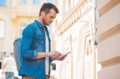 side view of man in denim shirt using smartphone on street