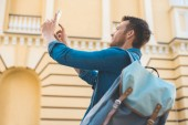 Photo handsome young tourist with backpack taking photo with smartphone on street