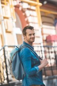 Photo Attractive young tourist with backpack walking by street and looking at camera