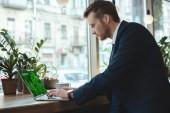 boční pohled na koncentrované podnikatel pracuje na notebooku s on-line obchodu nápis na obrazovce u stolu s šálkem kávy v restauraci