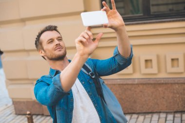 attractive young tourist with backpack taking photo with smartphone on street
