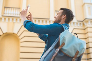 handsome young tourist with backpack taking photo with smartphone on street
