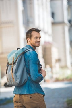 Smiling young man with backpack walking by street and looking at camera stock vector