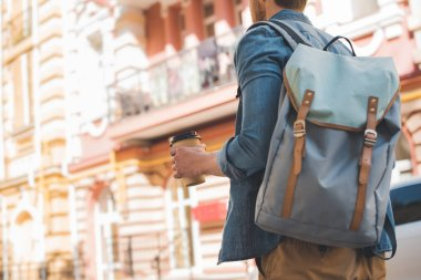 cropped shot of young man with backpack and coffee to go walking by street