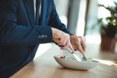 Fotografie částečný pohled podnikatel u stolu se podává oběd v restauraci