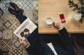 Fotografie overhead view of businessman with newspaper sitting at table with cup of coffee and smartphone in cafe
